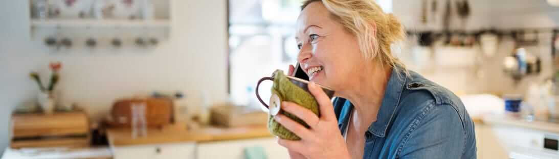 Woman on phone holding drinking mug